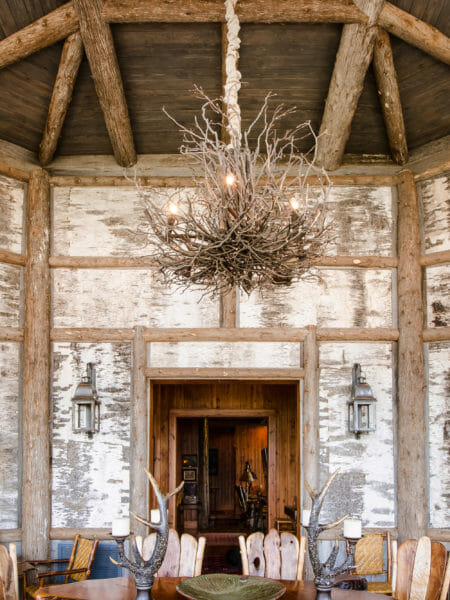 Decorative textured birch bark wall panels in a rustic traditional sun room. Bark intact poles accent the walls.
