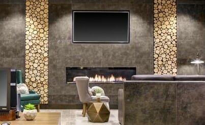 Bark House Poplar Pole End Cut Wall Panel around fireplace. Designer: Earth Elements